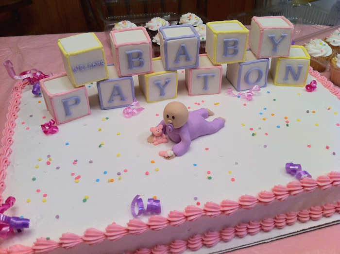 confetti in different colors, strewn on a white cake, with pink frosting, baby shower sheet cakes, decorated with a fondant baby figurine, in a purple onesie, and several alphabet blocks, in different colors, spelling out a festive message