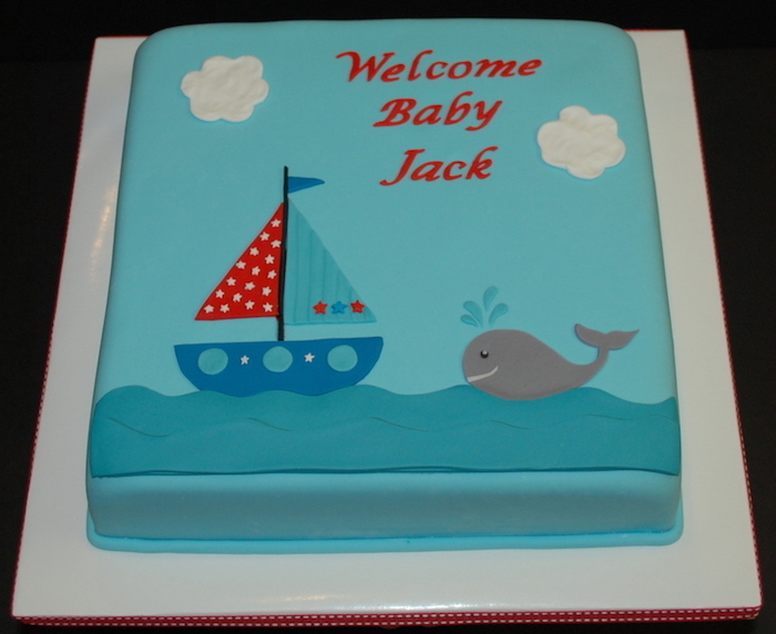 sailing boat in blue, red and turquoise, decorated with little stars, on a light blue square cake, nautical baby shower cakes, with a little grey whale, and a festive message in red