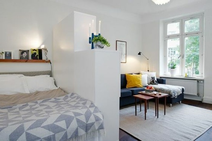 corner sofa in dark blue, with white and yellow cushions, and two small coffee tables, living room furniture for small spaces, sleeping area separated by a white wardrobe