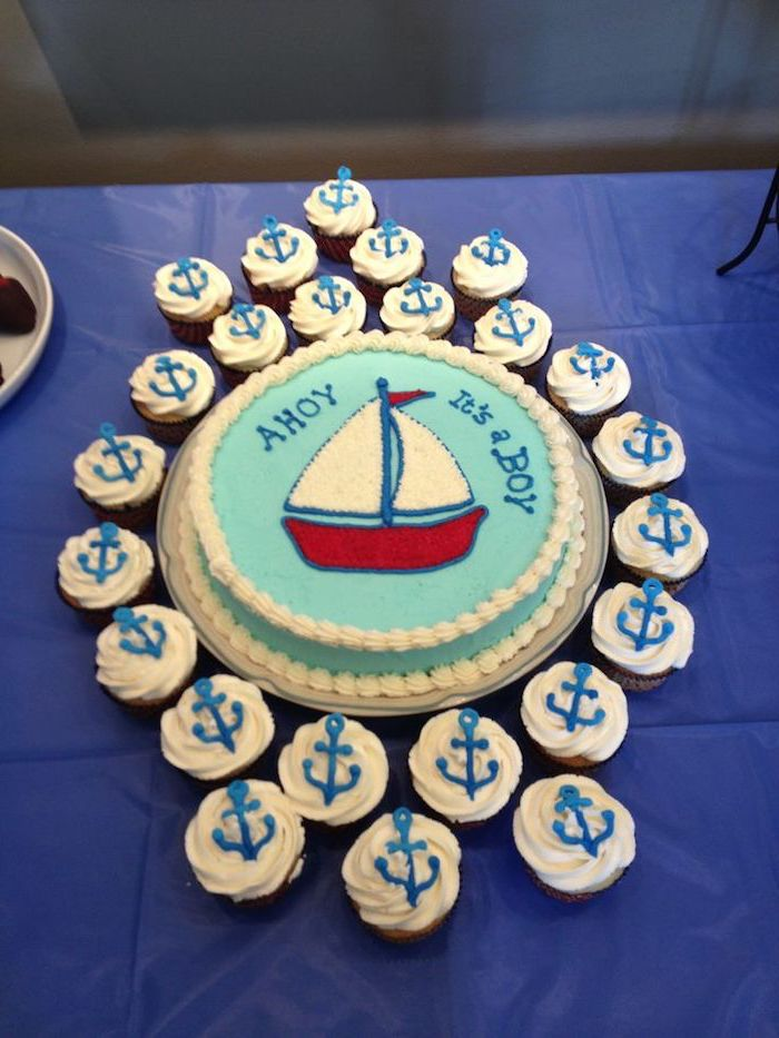 ahoy it's a boy, written in blue frosting, on a round pale turquoise cake, with a red and white drawing of a sailing boat, nautical baby shower cakes, surrounded by cupcakes topped with anchors