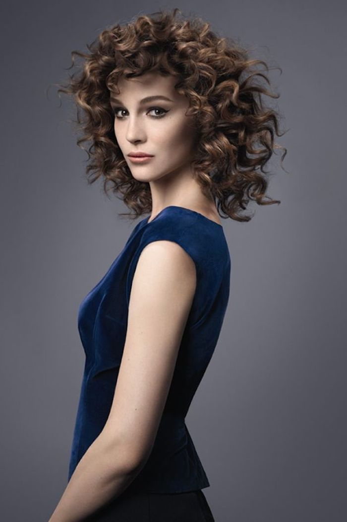 velvet sleeveless dress, in dark navy blue, worn by woman with brunette hair, and dark blonde highlights, short haircuts for curly hair, dark grey background
