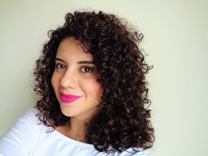fuchsia pink lipstick, worn by smiling, naturally curly woman, with dark brunette ringlets, and deep side part, dressed in white, boat neck jumper