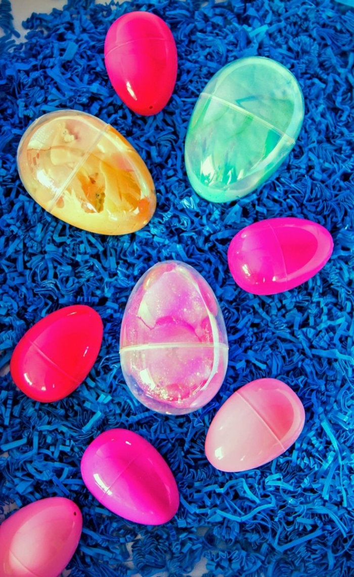 plastic easter eggs, six in different shades of pink, and three larger clear ones, all containing diy moulding goo, fluffy slime
