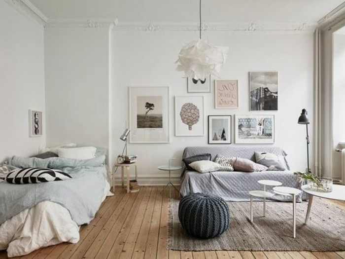 scandinavian style room, with a beige wooden floor, a bed in pale blue, sofa with a light lavender-colored cover, and several cushions, room setup ideas, framed artwork and coffee tables