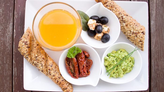 mediterranean breakfast on a tray, with large glass of orange juice, two pieces of bread, and three small white dishes, containing guacamole and sun-dried tomatoes, olives and marinated cheese