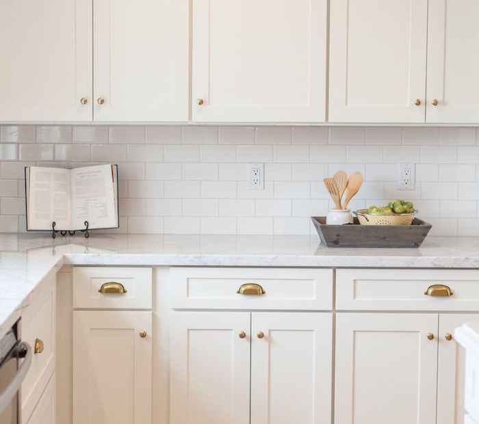 book on a black metal stand, placed on a white marble counter, in kitchen with white cabinets, white subway tile pattern on the wall, little grey wooden box wth utensils