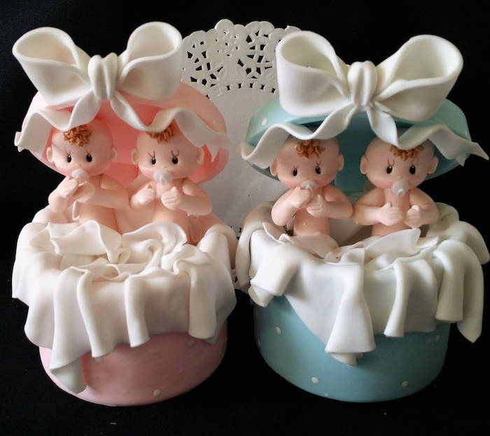 twin baby shower cakes, cake toppers in white and pink, and white and blue, shaped like opened gift boxes, with white bows, with a set of two baby figurines in each