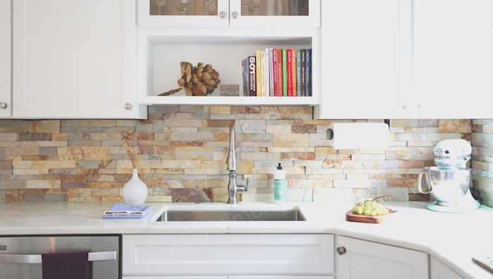 stacked stone backsplash, in beige and grey tones, in a kitchen with white cabinets, and matching white counter tops