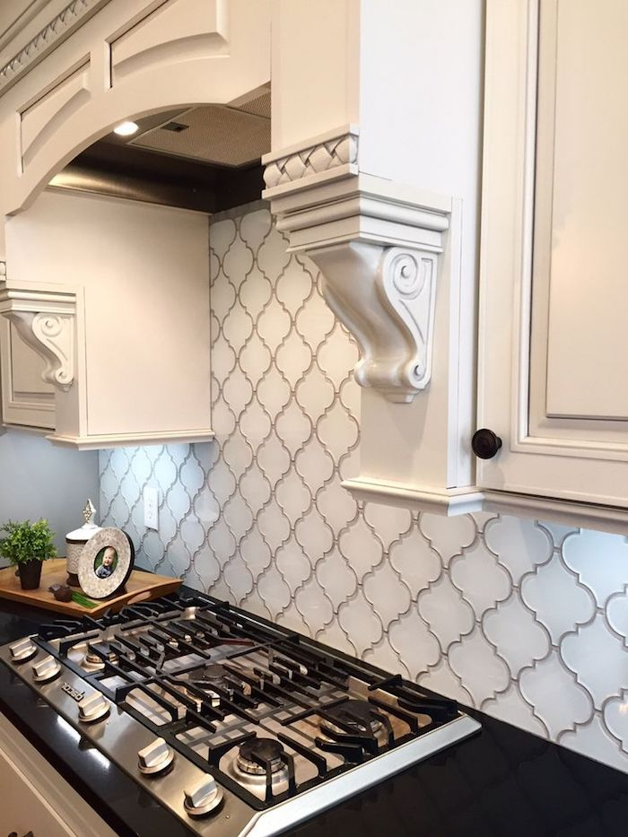 arabesque backsplash in white, with grey joints, near a black counter top, with an inbuilt hob, and white cabinets, with ornamental details