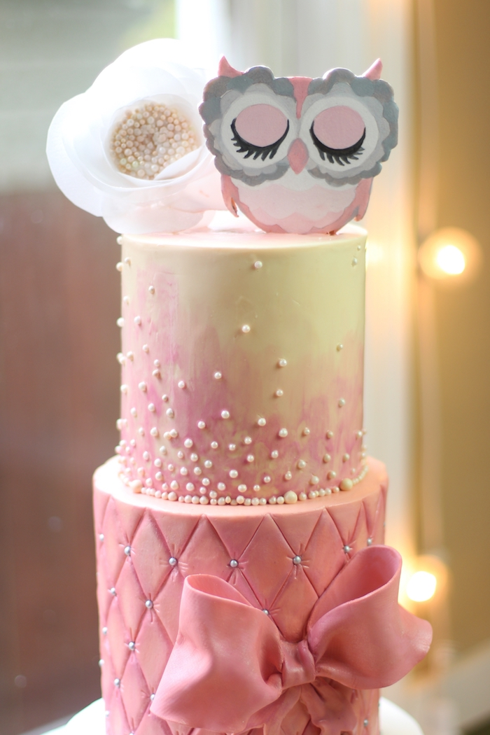 owl baby shower cake, in pale pink, and light cream, decorated with a large fondant bow, white edible pearls, a large faux white flower, and a pink owl figurine