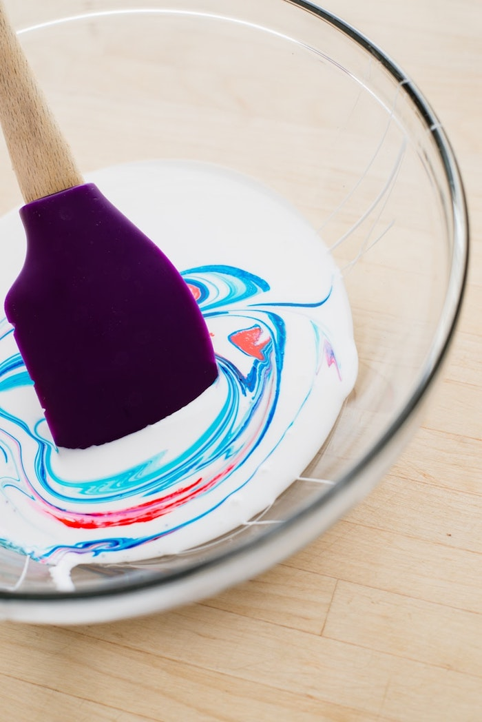mixing red and blue paint, in a clear glass bowl, with white compound, fluffy slime recipe, using a purple plastic spatula