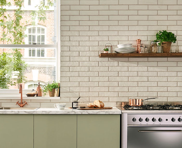 khaki green kitchen cabinets, pale and smooth, in a room with a shiny metal oven, tiled wall in cream, wooden shelf with utensils