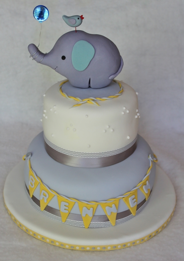 balloon in metallic blue, held by a grey elephant figurine, with turquoise ears, placed on top of a layered cake, with pale grey and yellow details
