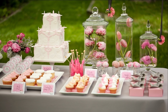baby shower cakes for girls, a selection of different cupcakes and pastries, in pink and white, on a grey table, near a three-layered cake, and several flower vases