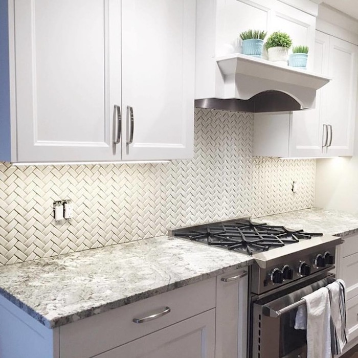 off white kitchen backsplash, with small tiles, in a herringbone pattern, stove and white cabinets, grey and white counter top