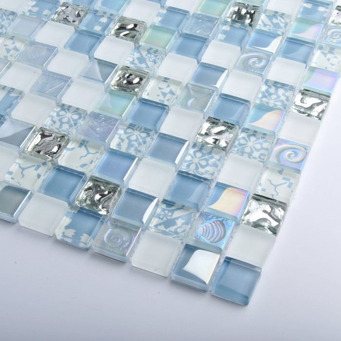 shades of blue and silver, on small square tiles, sheer and opaque, glass mosaic tile backsplash example, placed on a white surface