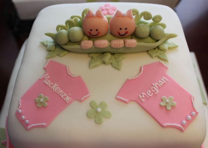 mackenzie and meghan, written in white, on two pink onesies, decorating a smooth white, square-shaped cake, twin baby shower cakes, topped with a green pea pod, containing two baby figurines