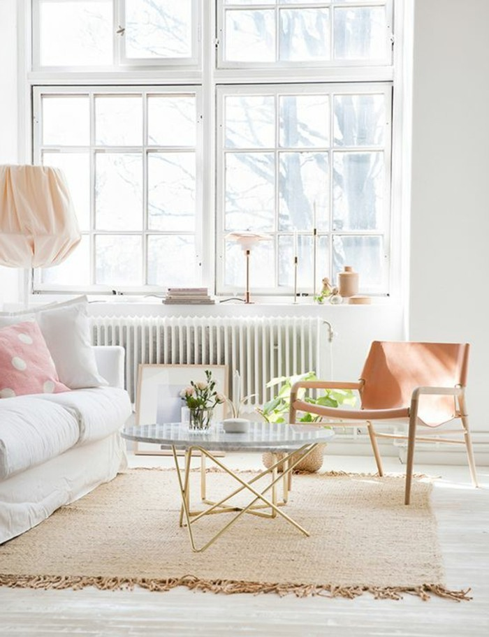 rug in beige with tassels, inside a bright room, with large windows, containing a white sofa, a coffee table, and a peach-colored chair