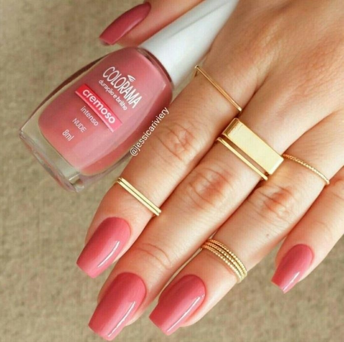 square tips on oval nails, painted in peach pink nail polish, on a hand with several square and round gold rings, holding a bottle of nail polish