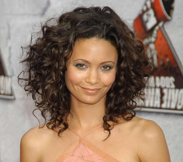 thandie newton smiling, in a nude pink strappy top, wearing discrete make up, hairstyles for short curly hair, shoulder length brunette curls