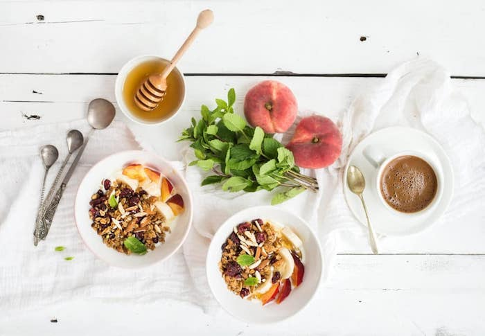 sprigs of mint and two peaches, near a bowl of honey, and a cup of coffee, healthy low calorie breakfast, two bowls of muesli, covered with fruit