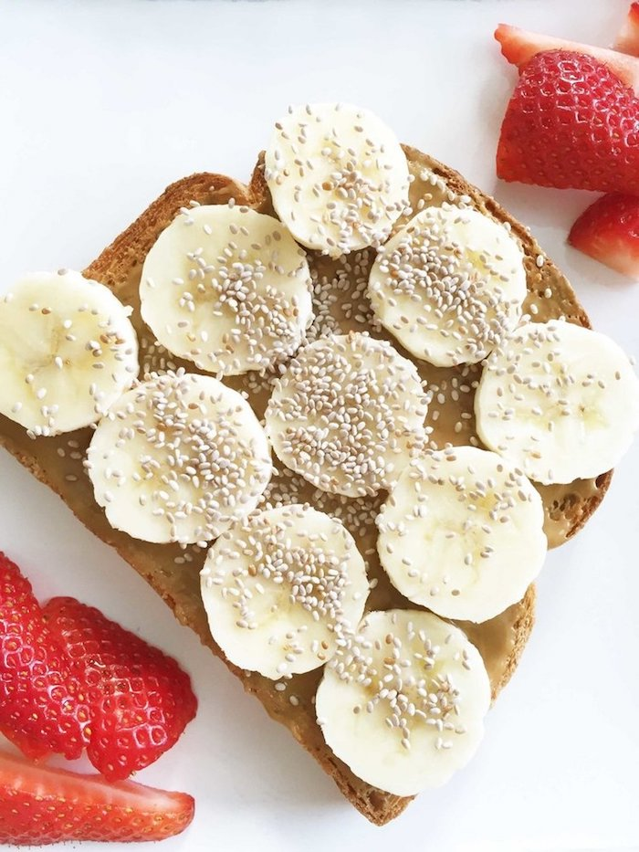 sesame seeds on slices of banana, on top of a piece of toast, smeared with peanut butter, easy breakfast recipes, next to several pieces of strawberry