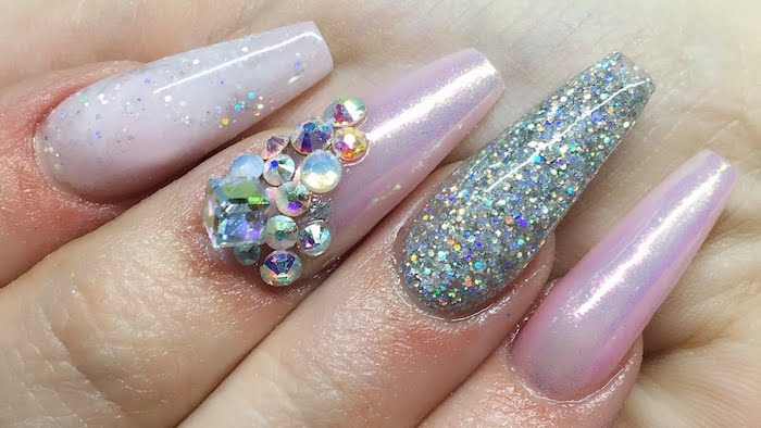 extreme close up, of four finger tips, with acrylic nail shapes, painted in milky pale pink nail polish, decorated with iridescent glitter, and pearly pink nail polish, decorated with rhinestones