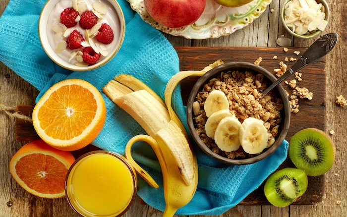 half-peeled banana near a halved orange and kiwi, brown bowl with muesli and banana slices, healthy breakfast ideas, cup with yoghurt and raspberries