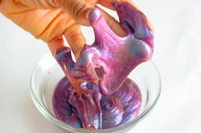metallic-effect galaxy slime in pink, with hints of blue and orange, how to make slime with shaving cream, stuck to the fingers of a hand, holding it over a glass bowl with more slime