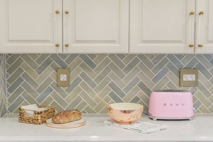 rose gold metallic bowl, with a wooden spoon, near a candy pink toaster, on a light counter top, with a herringbone backsplash, in different tones of grey