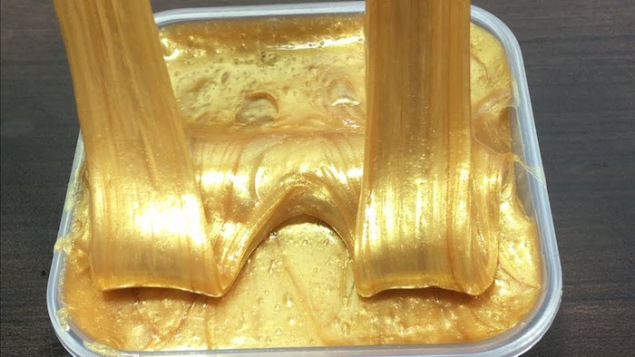 golden elmer's glue slime, smooth and shiny, two parts of it stretched upwards, inside a square clear plastic container