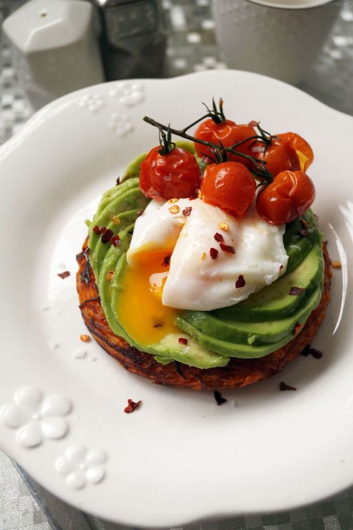 baked cherry tomatoes on the vine, on top of a poached egg, on a bed of avocado slices, low calorie breakfast, piece of toasted bread