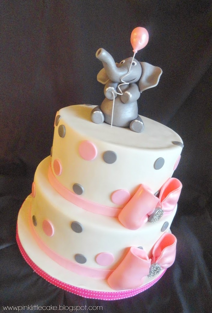 grey fondant figurine of an elephant, holding a pale pink balloon, on top of a layered cake, covered with white frosting, and decorated with pale pink, and light grey polka dots, and two pink ribbons with bows