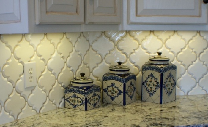 cream-colored arabesque tile backsplash, with a slight 3D effect, near off-white cabinets, and a stone-like, cream and grey counter top, with three porcelain jars