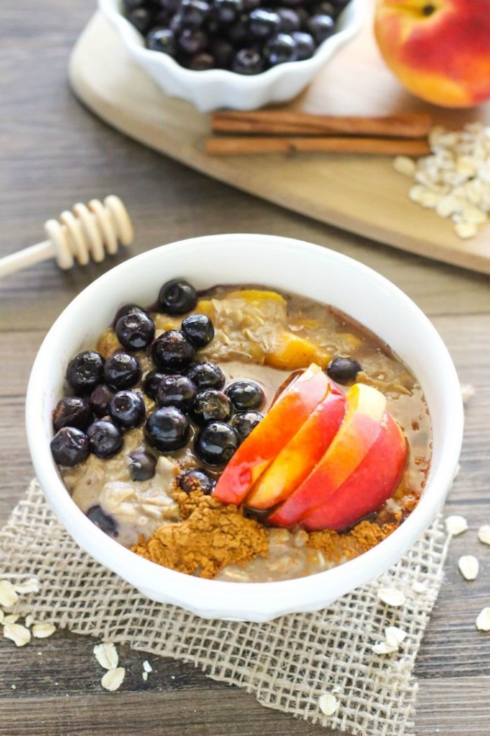 honey and blueberries, sliced peach and granola, on top of some porridge, made with rolled pats, breakfast menu ideas, ingredients in the background