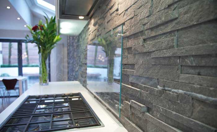 pewter grey stacked stone backsplash, with a clear glass protector, near a white counter top, with a black inbuilt hob