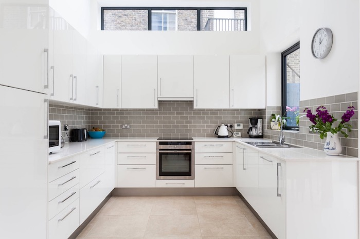 mink brown subway tile kitchen backsplash, in a room with a high ceiling, white kitchen cabinets, and beige tiled floor