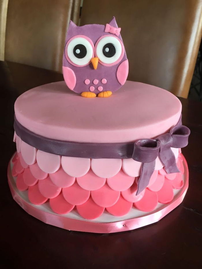 wide-eyed owl figurine, made from purple and pink fondant, with a little pink bow, topping a smooth cake, in four shades of pink, owl baby shower cake, dark purple fondant bow
