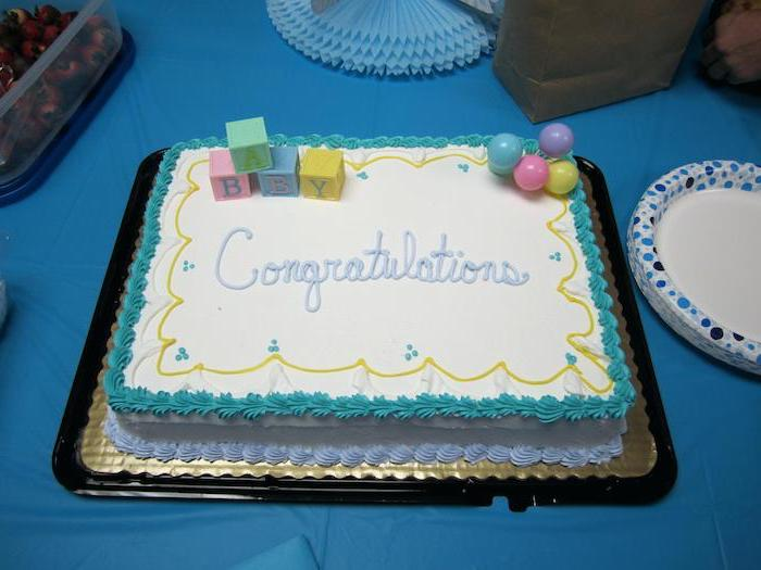 congratulations written in pale blue frosting, on rectangular white sheet cake, with teal and light blue details, and colorful fondant shapes