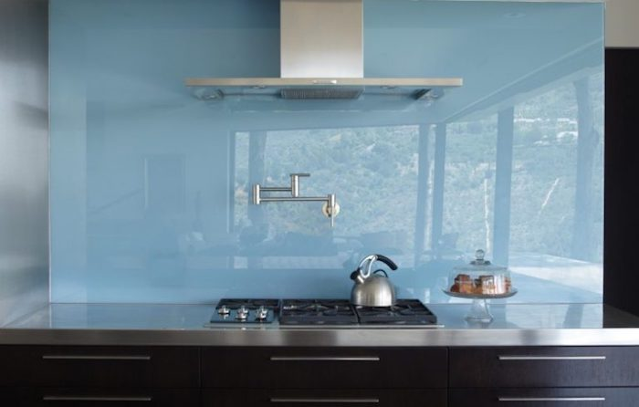 sky blue opaque glass backsplash, smooth and reflective, in a kitchen with black cabinets, a metal counter top, modern faucet and extractor hood