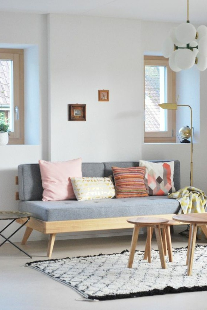 four cushions on a pale grey sofa, inside a room with white walls, and a smooth white floor, couches for small living rooms, black and white fluffy rug, three small wooden coffee tables