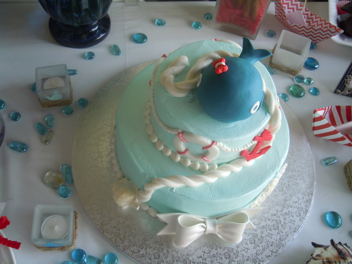 rope and a string of pearls in white, an anchor and a lifebelt, and a dark blue whale figurine, all made from fondant, and topping a creamy pale turquoise cake, nautical baby shower cakes, big white bow