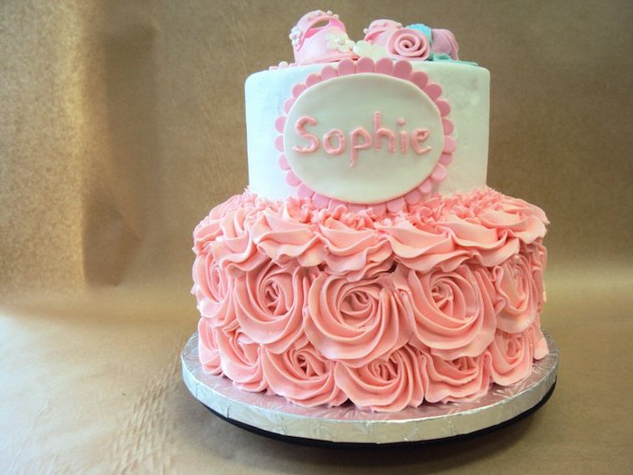 the name sophie written in pink frosting, on a two-layered cake, baby shower cakes for girls, decorated with pink frosted roses, tiny pink fondant shoes and flowers
