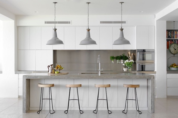 metal back splash, near smooth white cabinets, grey kitchen island, with an inbuilt sink, and four stools, three grey lamps, hanging from the ceiling