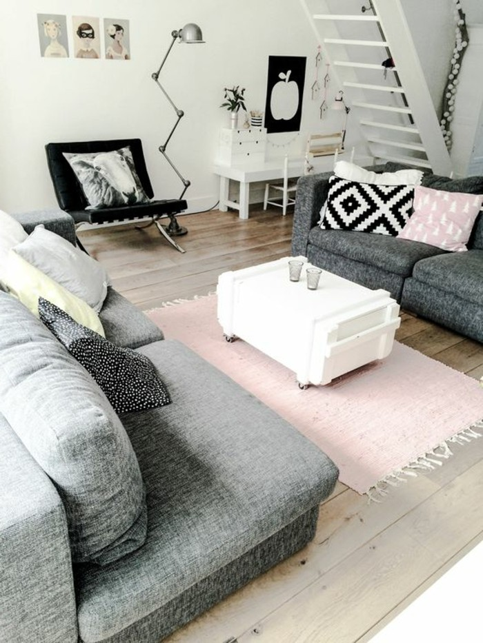 pastel pink rug and cushion, inside a room with grey sofas, simple living room designs, a black chair, white walls and a beige wooden floor