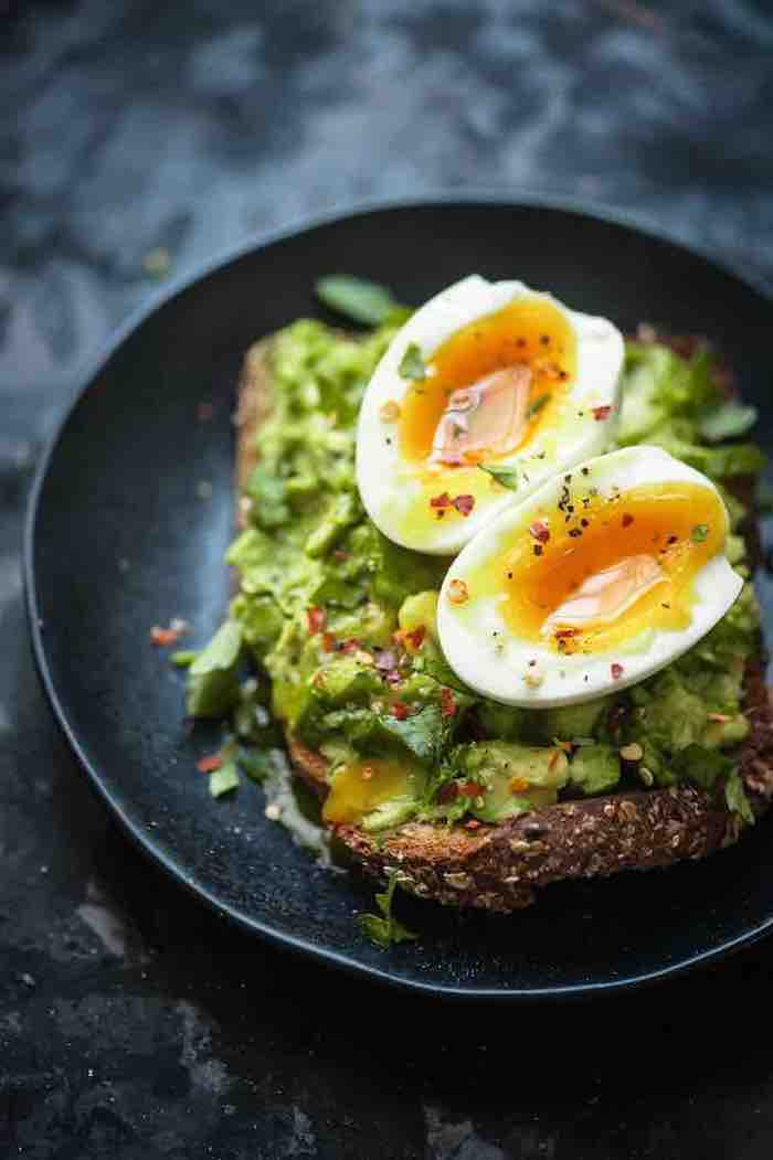 boiled eggs in halves, on top of a piece of bread, with a seasoned guacamole spread, with black pepper an chili flakes, in a black plate
