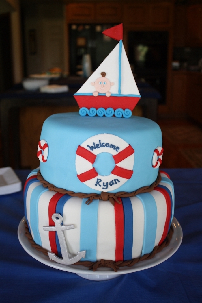 boat made from red, white and blue fondant, and containing a little baby figurine, topping a light blue, two-layered cake, decorated with an anchor and lifebelts