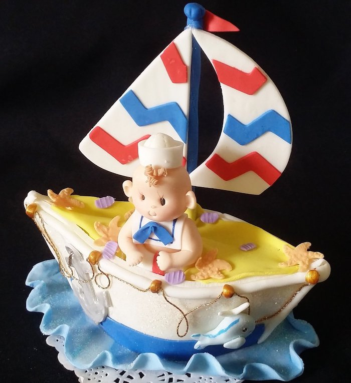 baby shower cake toppers girl or boy, a little fondant sailing boat, in white and red, blue and yellow, containing a smiling baby figurine, in a sailor's outfit