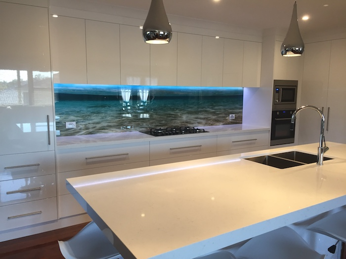 3D effect wall decal, depicting a seashore, creative kitchen back splash, near smooth white cabinets and drawers, and a matching kitchen island