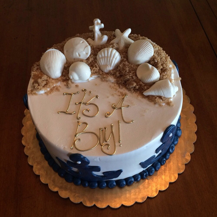 beach-inspired cake in white, decorated with dark blue anchors, sand made from brown sugar, and white shell, starfish and anchor shapes, made from fondant